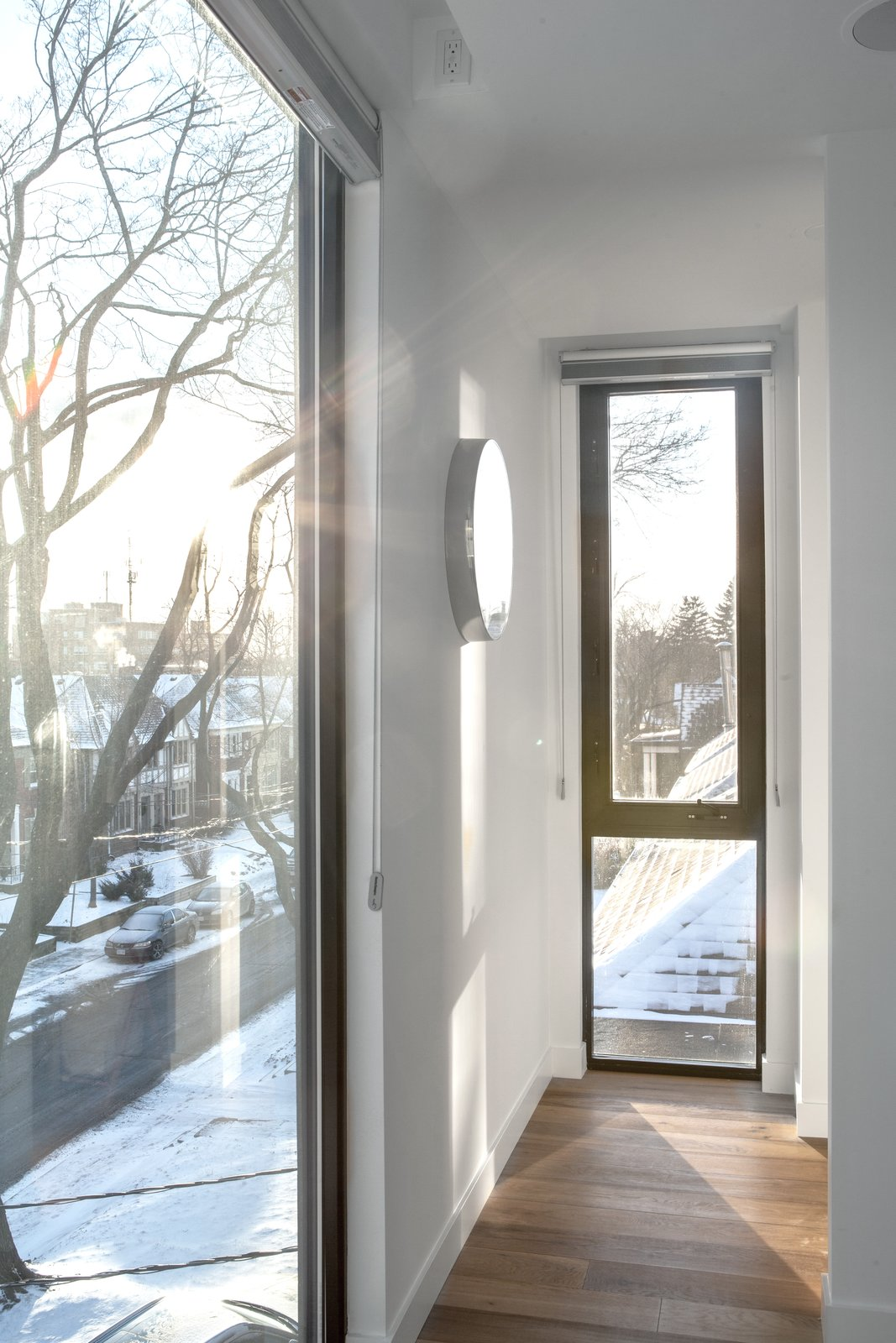 The master bedroom, situated at the front of the third-floor addition, is bathed in light from full-height windows. A slightly smaller window illuminates a nook leading to its walk-in closet.  Photo 9 of 9 in A Spacious Toronto Triplex Responds to Rising Urban Density