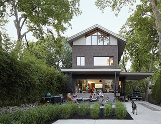 Matthew Hufft designed the house that he shares with his wife, Jesse, and their three children to sit inconspicuously among its neighbors in the Roanoke Park area of Kansas City, Missouri. The backyard and porch, which is furnished with a Saarinen Round Dining Table and Emeco Navy chairs, is a popular setting for warm-weather entertaining.
