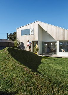 The house that Henri Sayes designed for himself and his wife, Nicole Stock, is distinguished by a cutaway in the cedar cladding that mirrors the angular double-height space within. In the yard, a grassy berm, fashioned from earth excavated for the foundation, takes the place of a fence.