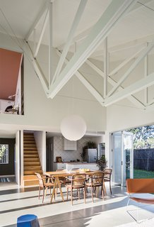 The inverted trusses subtly establish distinct spaces in the great room, with the bottom edges lending an intimate feel to the living area. A simple rice-paper lamp shade hangs above a kauri wood tabletop that the couple borrowed from Stock's aunt and uncle and set on a set of Taurus legs from Nils Holger Moormann. A Brit Longue chair by Sintesi isat is at the right.