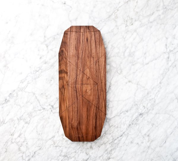 The Ray Long Board is characterized by its use of geometric shapes and angles. Designed to be used to present bread, cheeses, charcuterie, and other small appetizers, the board features beveled edges that make it easy to pick the board up off of the table. The top of the board is etched with a series of lines, which create a graphic visual statement of angles and intricate shapes. In addition to being admired, these shapes can also be used as borders to separate different types of cheese or meat, giving them a distinctive function as well.