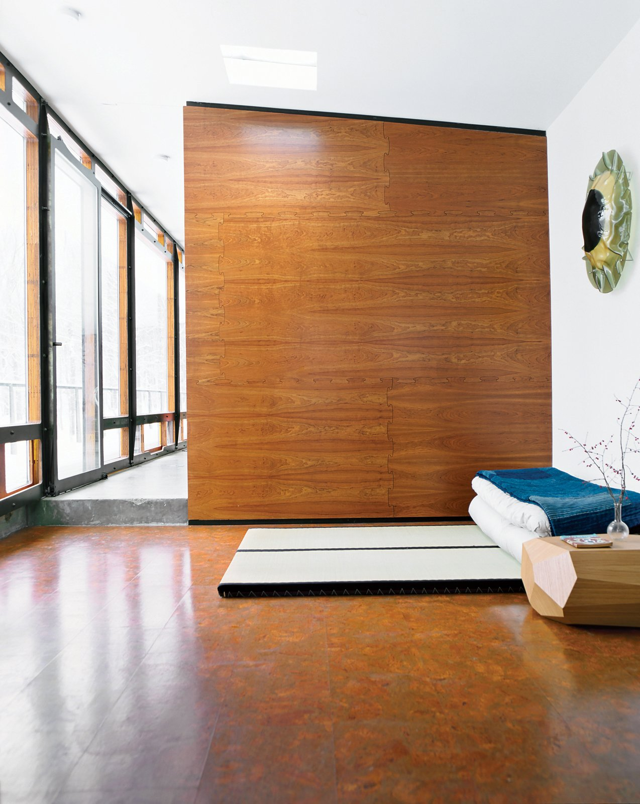 """Bedroom and Bed For one of two sleeping areas flanking the main living space, Wooten placed tatami from Miya Shoji on the cork floor. """"With the radiant heating system, it's fantastic to be in this glass box looking out at a blizzard, walking barefoot on the warm floor,"""" he says. """"Tatami are not for everyone, but they are really comfy to me. Before we built the house, I stayed at a traditional bed-and-breakfast in Kyoto, Japan, and had one of the best nights of sleep ever, so I decided I wanted to do that style of bed. On top is a 150-year-old Japanese denim patchwork quilt I bought from a friend who took me to Japan. I've always admired Japanese design—Noguchi is one of my favorites—so I was inspired to have that spirit in the house."""" miyashoji.com  Photo 11 of 12 in A Hybrid Prefab Home in Upstate New York"""