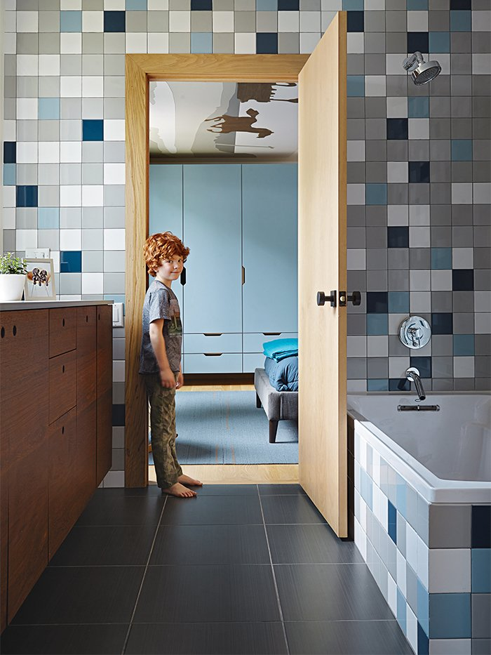 "Bath Room and Ceramic Tile Wall Rock stands in the doorway to the boys' bathroom, which is lined with semi-gloss Modern Dimensions tiles from Daltile. ""We wanted it to be playful,"" Hufft says, ""so we chose each color and laid out the tile distribution in Photoshop.""  Photos from This Kansas City Home Looks Like Its Neighbors, But Reveals a Truly Modern Sensibility"