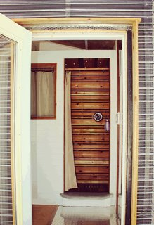 The shower, as seen through the main entrance. The metal-mesh open-joint rain screen is designed to rust over time.