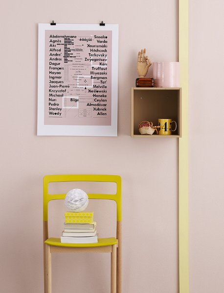 A pink and yellow interior close-up with various ephemera such as a movie director typography poster, paper beehive ball, wooden beads, and a models artist hand sculpture. Photo by: Magnus Anesund