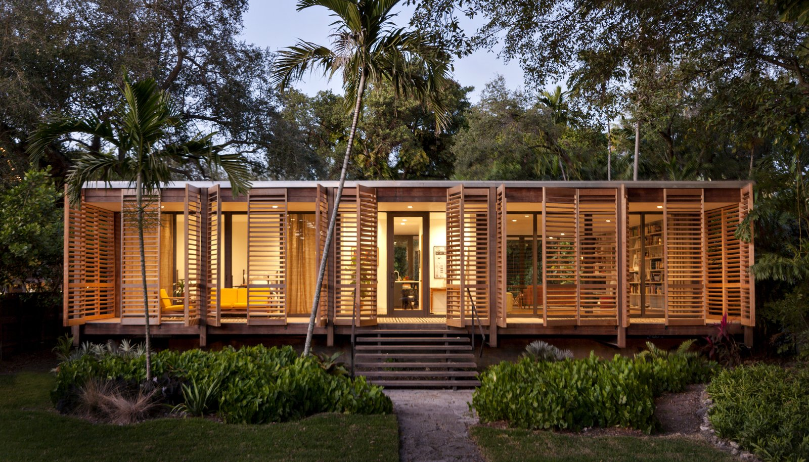 The 1,500-square-foot home features a striking interplay of sharp glass and soft wood shutters, creating a simple and practical building that's rich in cultural heritage. The home takes inspiration from many native building styles, including postwar tropical modernism, glass pavilion typology, and Florida cracker architecture. The dense ipe wood that clads the exterior and columns was chosen to withstand potential termite attacks and the damp tropical climate.  Mid Century Modern from Brillhart House