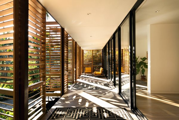 The semi-outdoor space extends the living room outward. Inside, a layer of glass sliding doors further facilitate breezes. The occupants can enjoy the sound and smell of rain behind shelter.