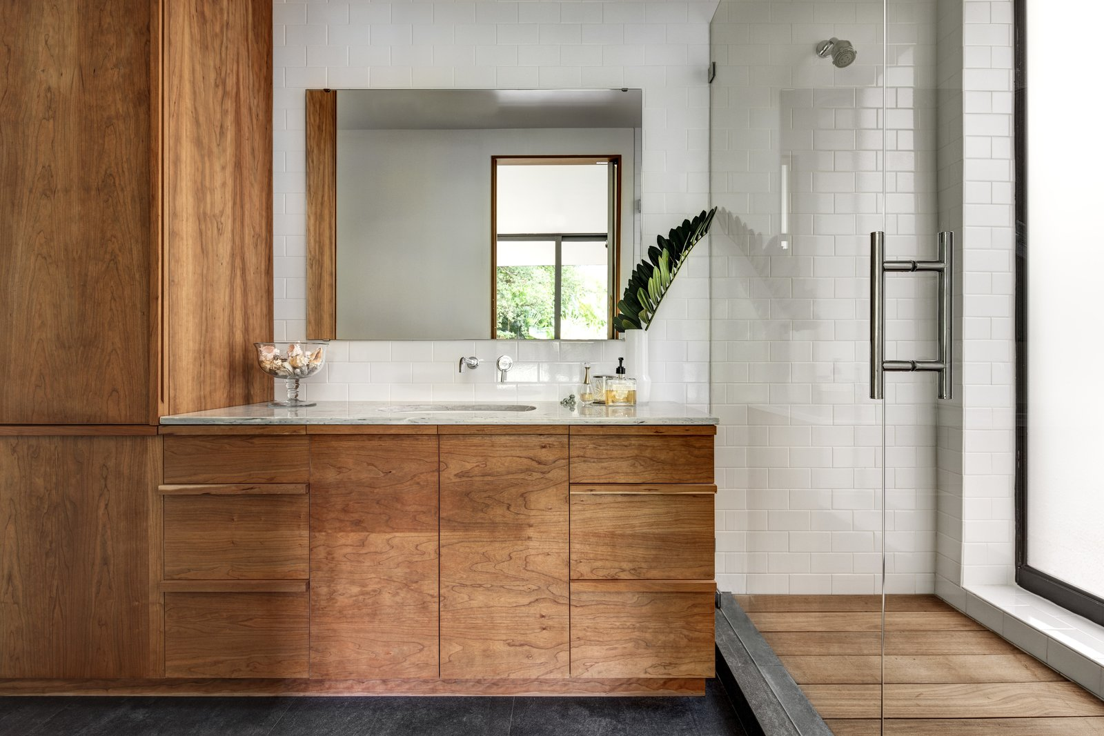 The master bathroom extends the same visual themes found throughout the rest of the home to keep the overall scheme unified. Ipe wood was used for the shower flooring and lightly oiled cherry wood forms the cabinets.  Brillhart House by Emma Janzen