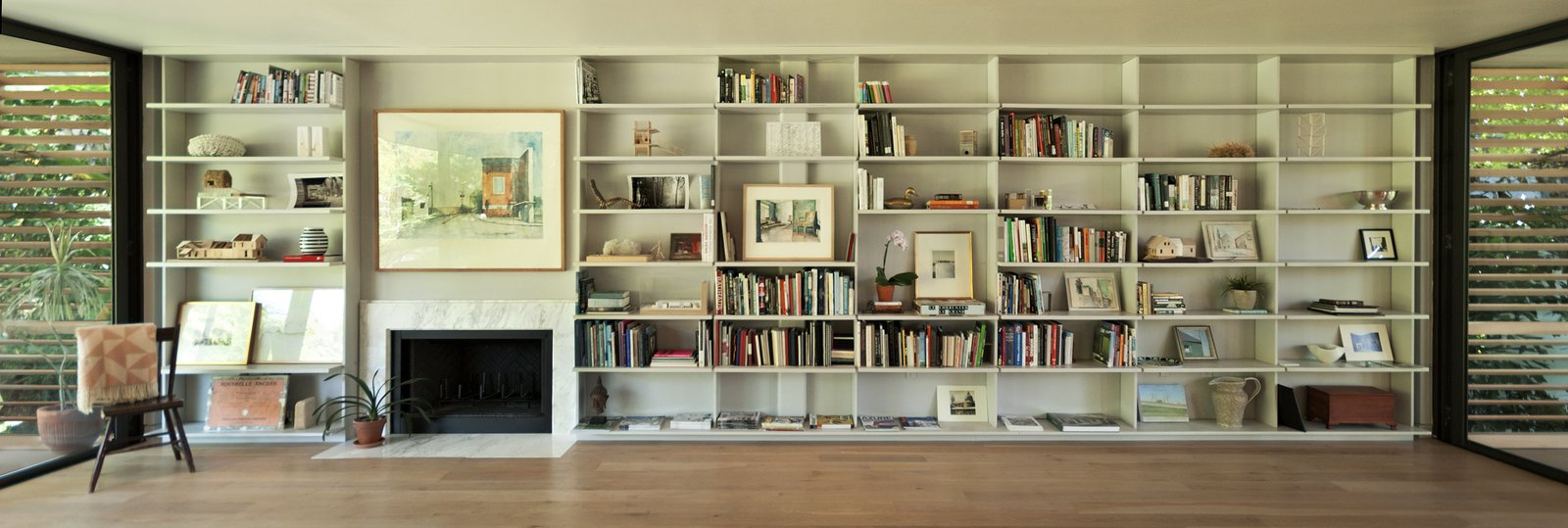 """In the living room, the Brillharts created a """"unified, simple and clean design"""" that incorporated a bookcase and fireplace along the continuous 30-foot long anchor wall. The shelves are inset several inches away from the glass walls on either side. Each individual layer cantilevers outwards to create a floating effect that mirrors the way the house itself floats above the ground.  Brillhart House by Emma Janzen"""