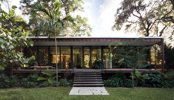 Between the front and rear exteriors, over 800-square-feet of patio space extend the living areas into the outdoors. From this angle, the references to Florida cracker architecture are obvious. The sleeping quarters are connected via a central corridor and kitchen to the living space on the other end of the building, a modern interpretation of the classic dogtrot house.