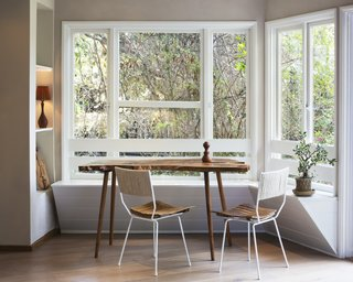 A previously empty space became a nature-infused breakfast nook with a built-in bench seat of wood slats painted white. Arthur Umanoff chairs join a live-edge wood slab table. The lines of the Dansk salt and pepper shaker are mirrored in the vintage lamp, with a cardboard shade found at the Long Beach flea market.