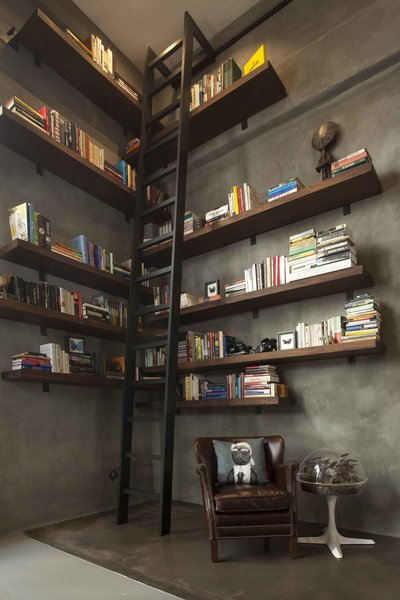 """A key request from the client was ample room for books. """"Brian had us promise that we would give him room to grow his collection,"""" the firm says. The solution was a large library with walnut shelves that was custom-built by woodworker Tom Clossey.  shelves"""