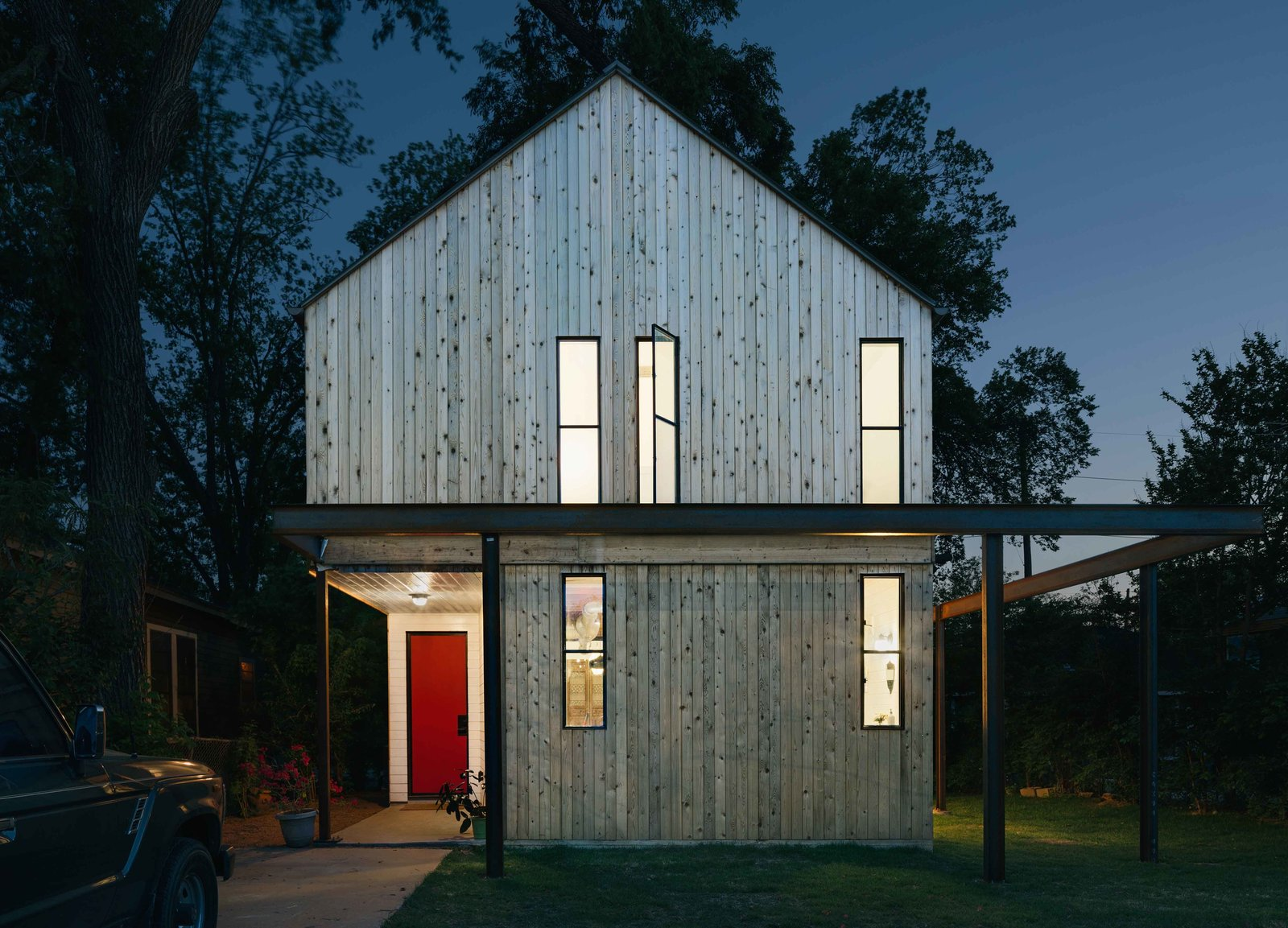 Exterior and House Building Type The streamlined shape of the home kept slab, framing, and roofing costs down, Pavonetti explains. A barn red shade on the front door adds a touch of farmhouse whimsy to the modern structure.  This Bright, Personality-Filled Home Was Built on a Budget in Austin by Esha Chhabra