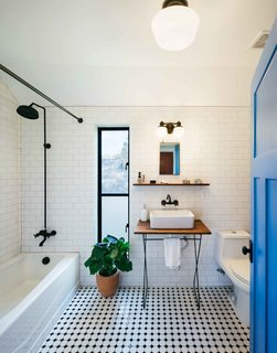 To create a bit more texture in the kitchen and baths, the couple added classic checkered tiles from the local hardware store—an inexpensive option that broke up the polished concrete floors spanning the rest of the house. Pavonetti designed and built the pedestal sinks using reclaimed cedar siding.