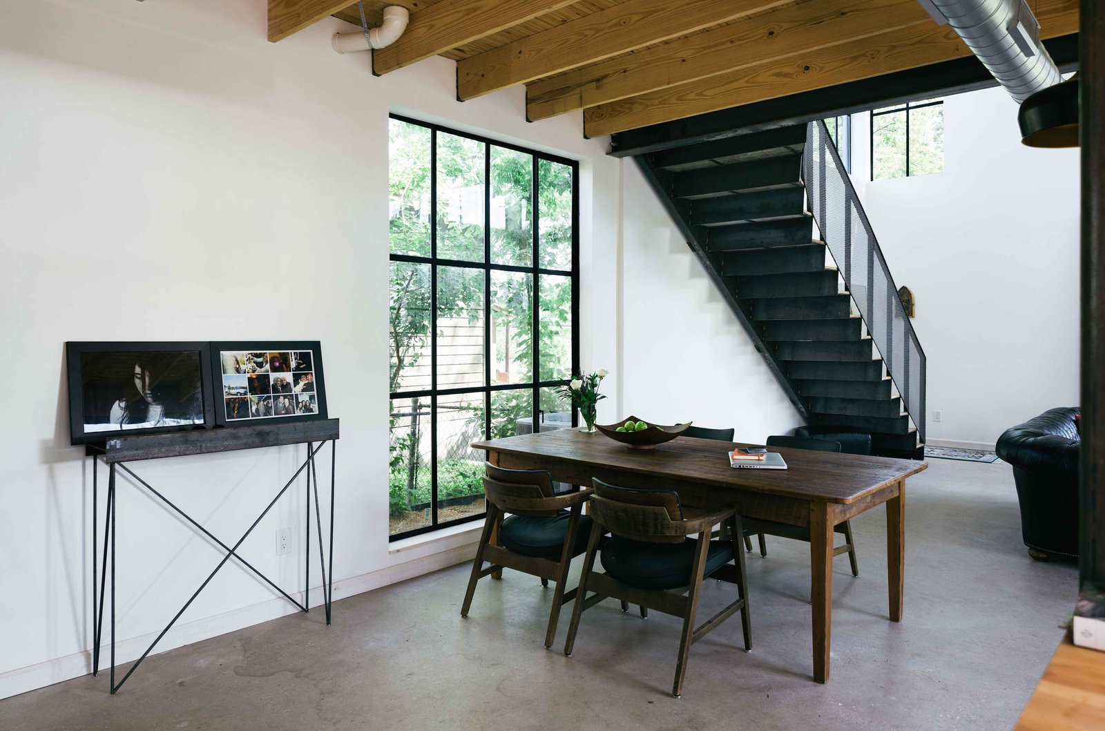 """Dining Room, Chair, Concrete Floor, and Table """"By providing a clean modern base of crisp white walls, the more rustic and industrial materials stand out and give warmth and nostalgia not found in a starkly modern home,"""" Pavonetti says.  190+ Best Modern Staircase Ideas from This Bright, Personality-Filled Home Was Built on a Budget in Austin"""