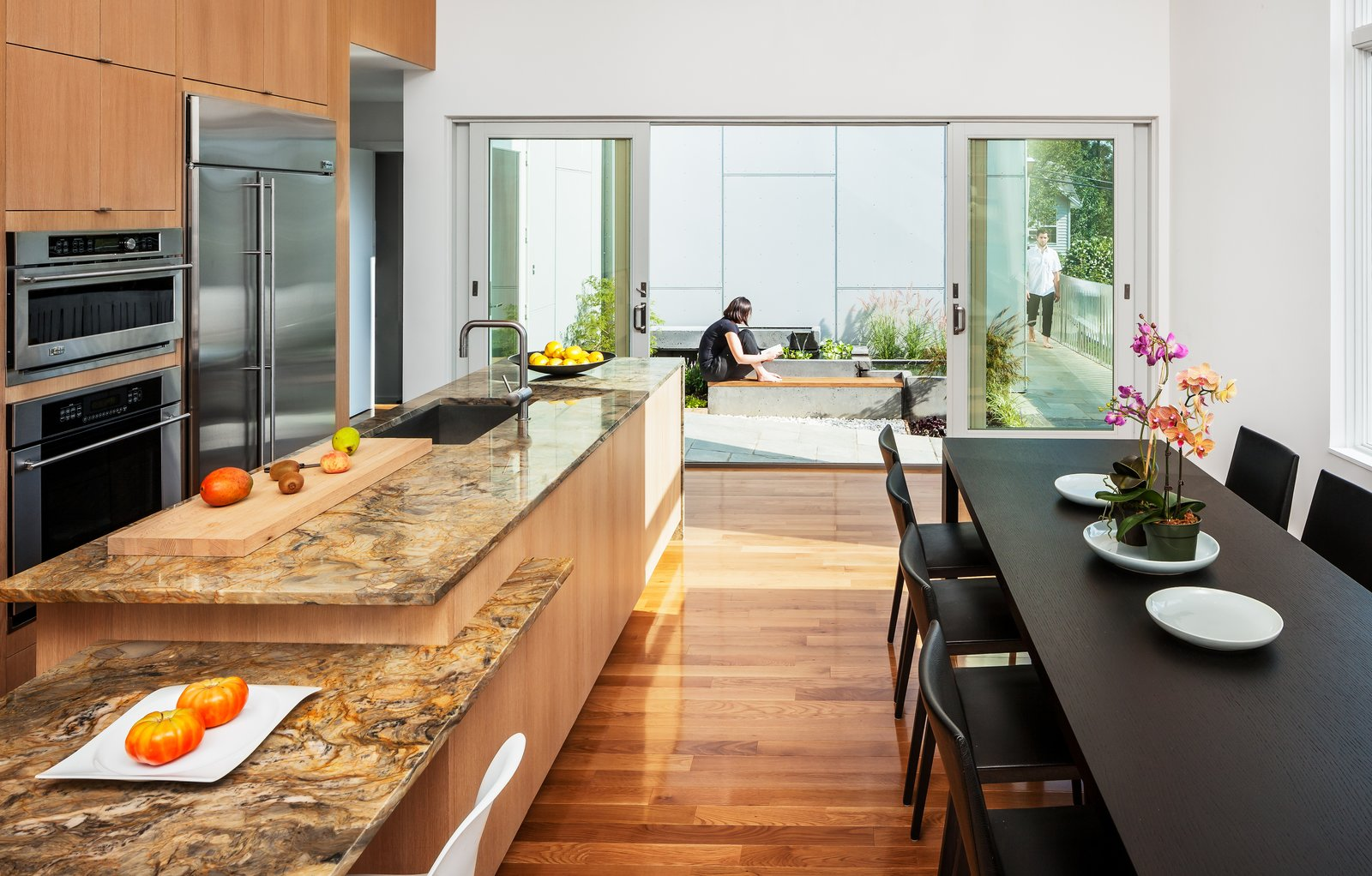 """Kitchen, Marble Counter, Medium Hardwood Floor, and Wood Cabinet To adhere to a limited budget, Höweler + Yoon used basic materials throughout—slate, concrete, wood, cement board—but splurged on a marble countertop in the kitchen. """"Because the house and millwork was so neutral to room could take a bit more richness,"""" says Yoon. From within the combined living/kitchen/dining area, one only sees the microcourtyard outside.  Photo 9 of 11 in Secret Garden"""