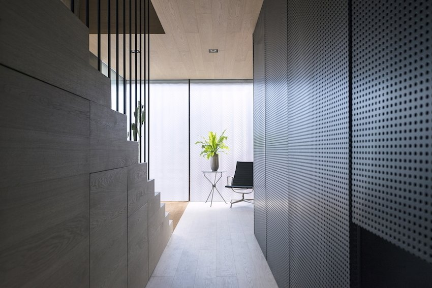 Hallway and Medium Hardwood Floor Though the minimal layout maxmizies open space, moments of contrast, such as the wood grain against the perforated metal divider, animate the interior.  Photo 5 of 10 in Super Minimal Steel and Concrete Villa with an Unusual Facade