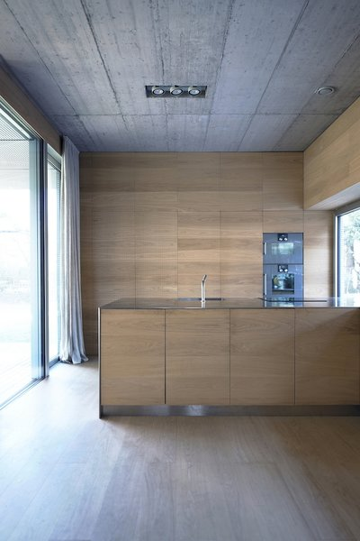 Oman and his partner Andrej Gregoric had the cupboards, stairs, and bed all custom-made. The interior casework provides storage and adds warmth to the concrete walls.
