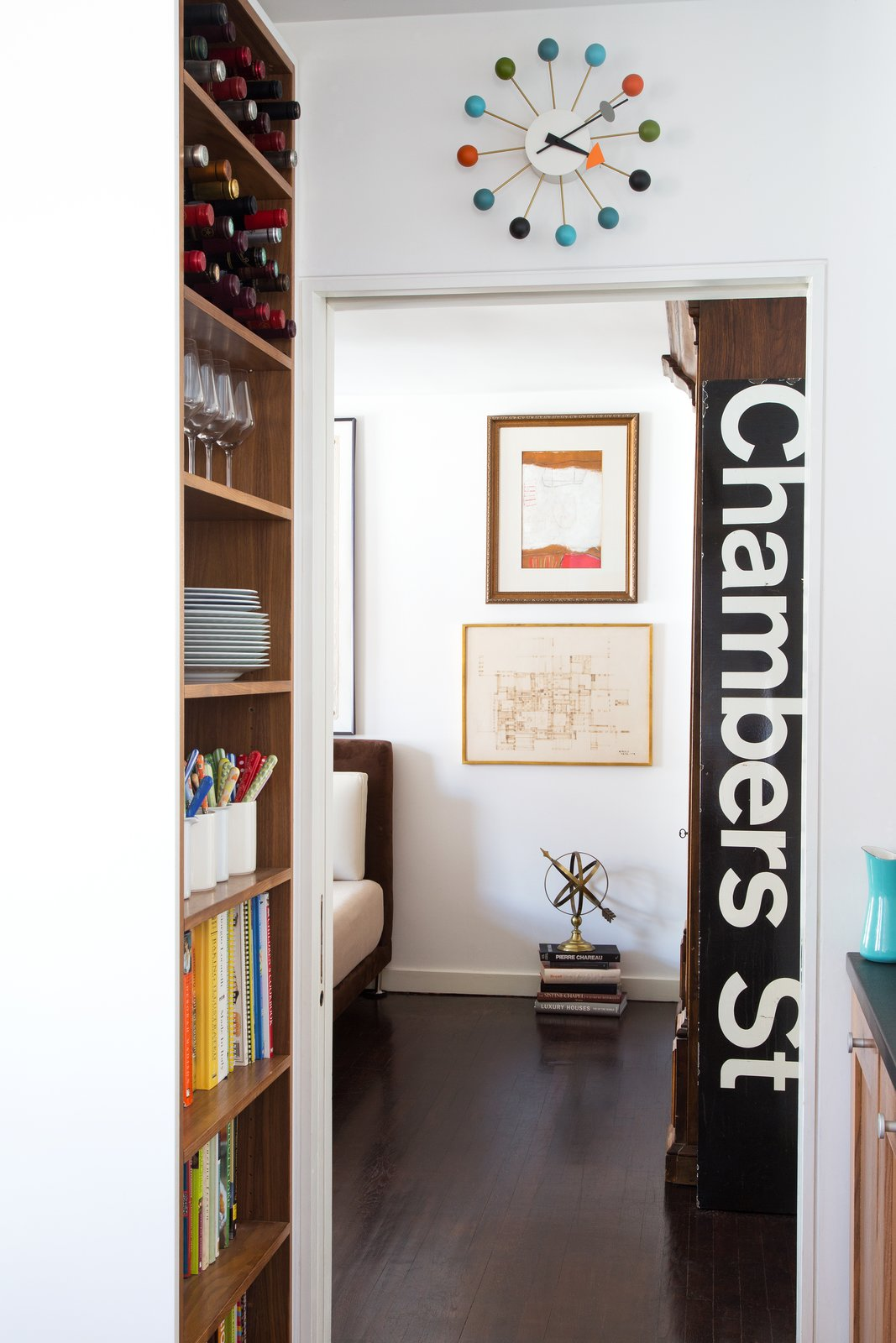 Hallway and Dark Hardwood Floor A Nelson Ball Clock and subway sign decorate one hallway.  Lovely NYC Abodes That Will Give You Apartment Envy by Allie Weiss from George Nelson's Ball Clock May Not Be His After All