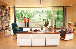 An architectural designer and an artist harnessed the collective power of their design firm to renovate a dilapidated mid-century gem into a hillside perch for their family.  Dieter Rams's modular 620 Chair Programme, from the 1960s, takes center stage in the Alford-Young family's living room. The set is accompanied by Artemide's classic Tolomeo floor lamp and a Portofino Bergère chair that was designed by Rodolfo Dordoni for Minotti. The rolling glass doors running the length of the room are from Fleetwood.  Photo by: Brent Humphreys