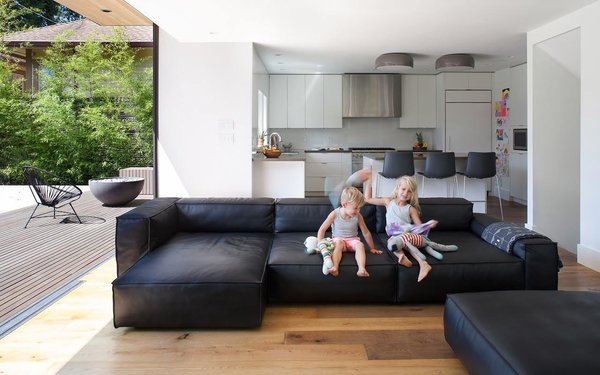 The addition of a living room beside the kitchen lets mom and dad spend more time with their kids – and watch over their activities. The children are sitting on a NeoWall couch by Living Divani, the light fixtures above the island are Smithfield by Flos, and the floor is oak.