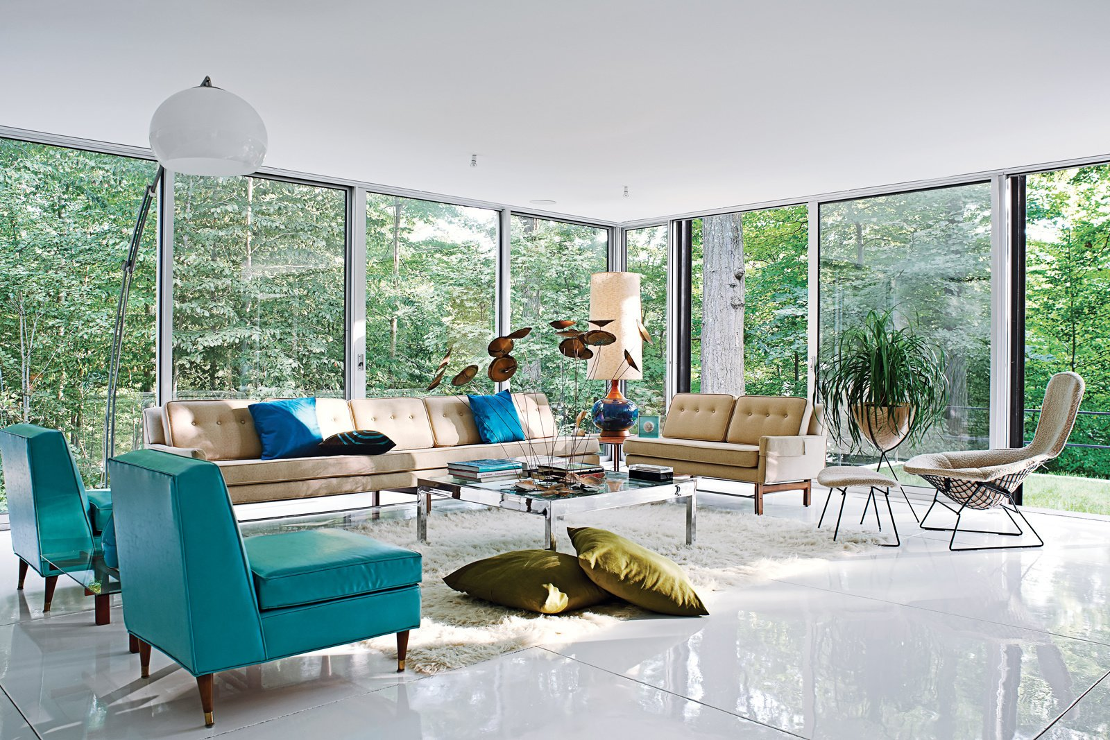The spacious living room, filled with vintage furnishings by Harry Bertoia, Paul McCobb, overlooks the heavily wooded site, which adjoins a protected watershed. Photo by: Jason Schmidt  47+ Midcentury Modern Homes Across America by Luke Hopping from Blues Clues