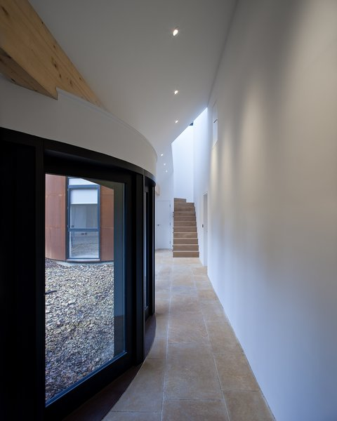 """A glass-fronted portico leads from the cottage's kitchen past four bedrooms to the new tower, accessed by a sculptural rectangular staircase. """"The courtyard glazing is designed to open up this walkway to the outside and to brake up its sense of division,"""" Whittaker says."""