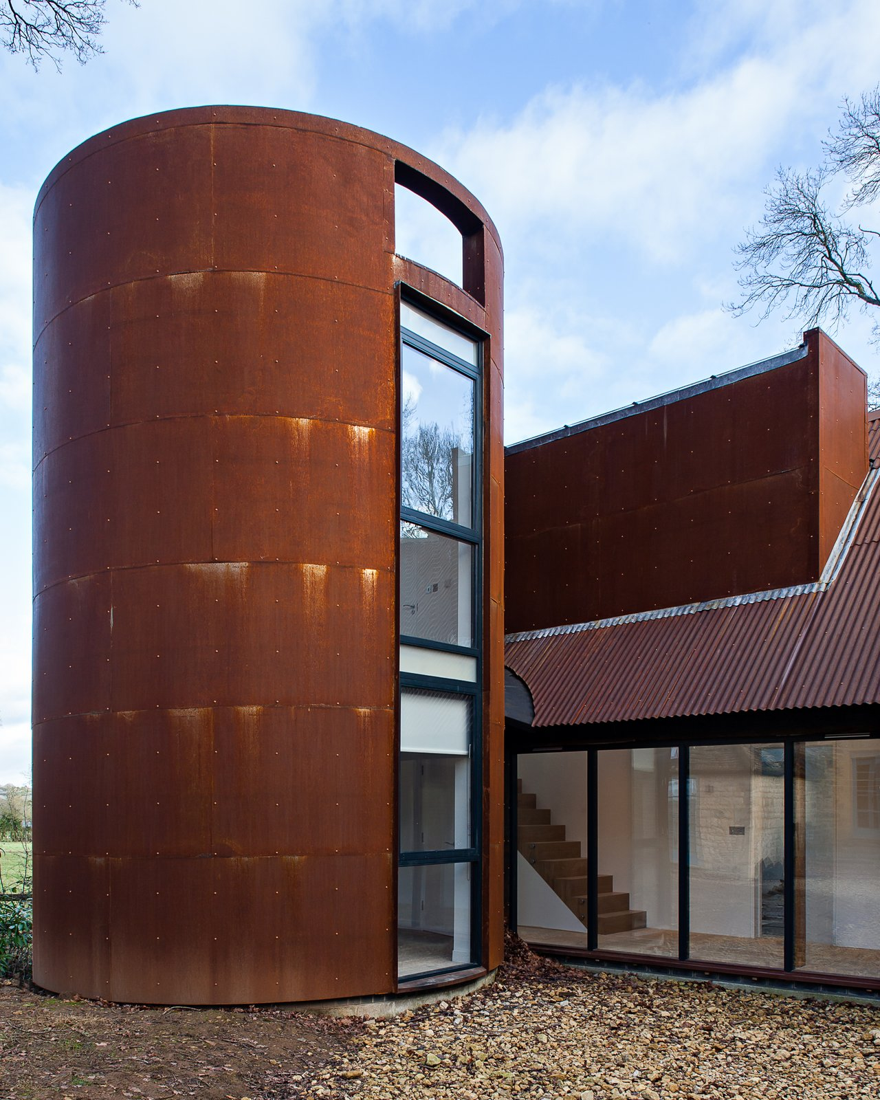 Exterior, Metal, Metal, and Barn A circular tower echoes the former gas storage cylinder that once occupied its place. It houses a private study.  Exterior Metal Barn Photos from This Modern Barn Looks Completely at Home in the English Countryside