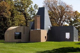 """The Wintons commissioned Gehry after reading about his work in The New York Times in 1982. It was the pick of a client with premonition, and as the final structure indicates, an open mind. The architect was asked to create a space for the Wintons' visiting family—five kids and plenty of grandchildren necessitated the extra room—and complement the main home, a brick Philip Johnson """"donut"""" on a 12-acre plot on the shores of Lake Minnetonka. But Gehry followed his own muse, and often talked about the home he created as pure sculpture, according to Victoria Young, the Professor of Modern Architectural History at St. Thomas University and Coordinator of Frank Gehry's Winton Guest House. """"Even the original models have all these disparate shapes,"""" she says. """"The first model he presented to them had a log cabin, referencing the fact that the Wintons' fortune came from Canadian lumber."""" Since it was a guest house, Gehry felt free to experiment. """"You can explore things in a way you can't in a place people live in all the time."""""""