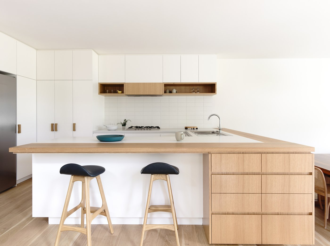 In the kitchen, black-cushioned bar stools by Erik Buch pop against the blonde wood counters, custom white melamine cupboards, and milky ceramic tile backsplash. The kitchen sink is by Franke, the faucet by Grohe, and the fridge by Liebherr.  Kitchen from Lush Hill