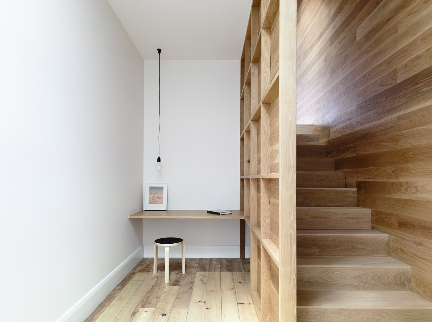 A central winding staircase connects the original house to the new addition. Exposed framing flanking the staircase creates an intimate study with plenty of shelving space. A Nud pendant light from Great Dane hangs above the built-in desk.  Lush Hill by Laura C. Mallonee