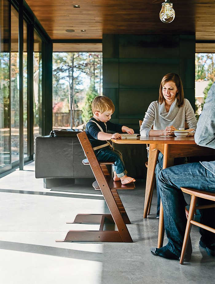 Dining Room, Table, and Concrete Floor Amy and Jeremy Clark join their son, Edison, in the dining room; the Thatcher chairs by Newport Furniture and a dining table by Caperton of West Virginia are both from Room & Board. Edison's high chair is the Tripp Trapp model by Stokke.  Photo 4 of 13 in Minimal North Carolina Home Built for a Tech-Forward West Coast Couple