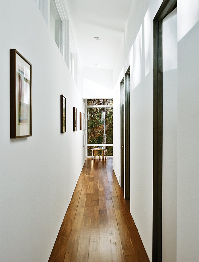 Hallway and Medium Hardwood Floor The interiors are painted in Sherwin-Williams Extra White Flat; flooring is five-inch walnut plank. A bentwood table and chairs are from ECR4Kids.  Photo 9 of 13 in Minimal North Carolina Home Built for a Tech-Forward West Coast Couple