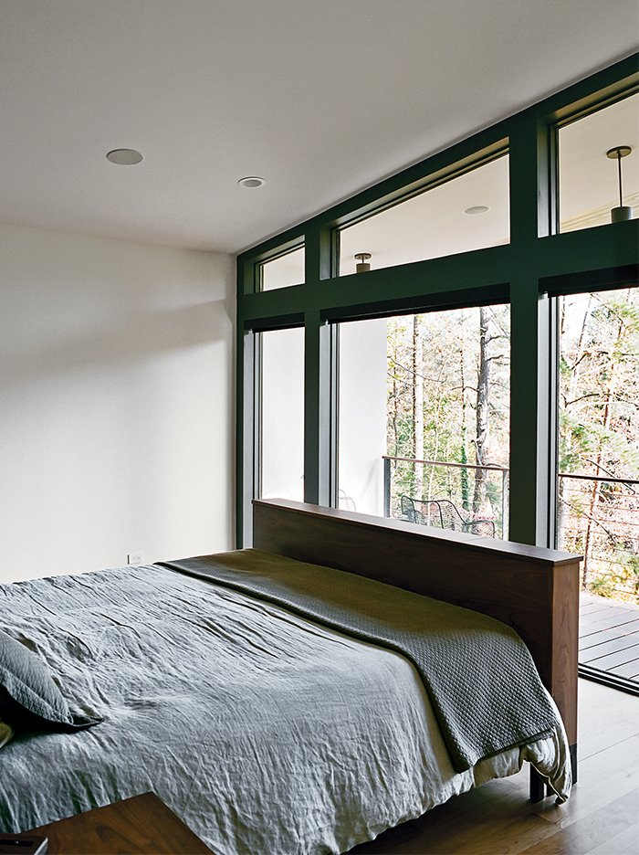 Bedroom, Bed, Medium Hardwood Floor, and Recessed Lighting The master bedroom, which overlooks a lake across the street, is furnished with a Copenhagen bed by Wood Products for Room & Board.  Photo 11 of 13 in Minimal North Carolina Home Built for a Tech-Forward West Coast Couple