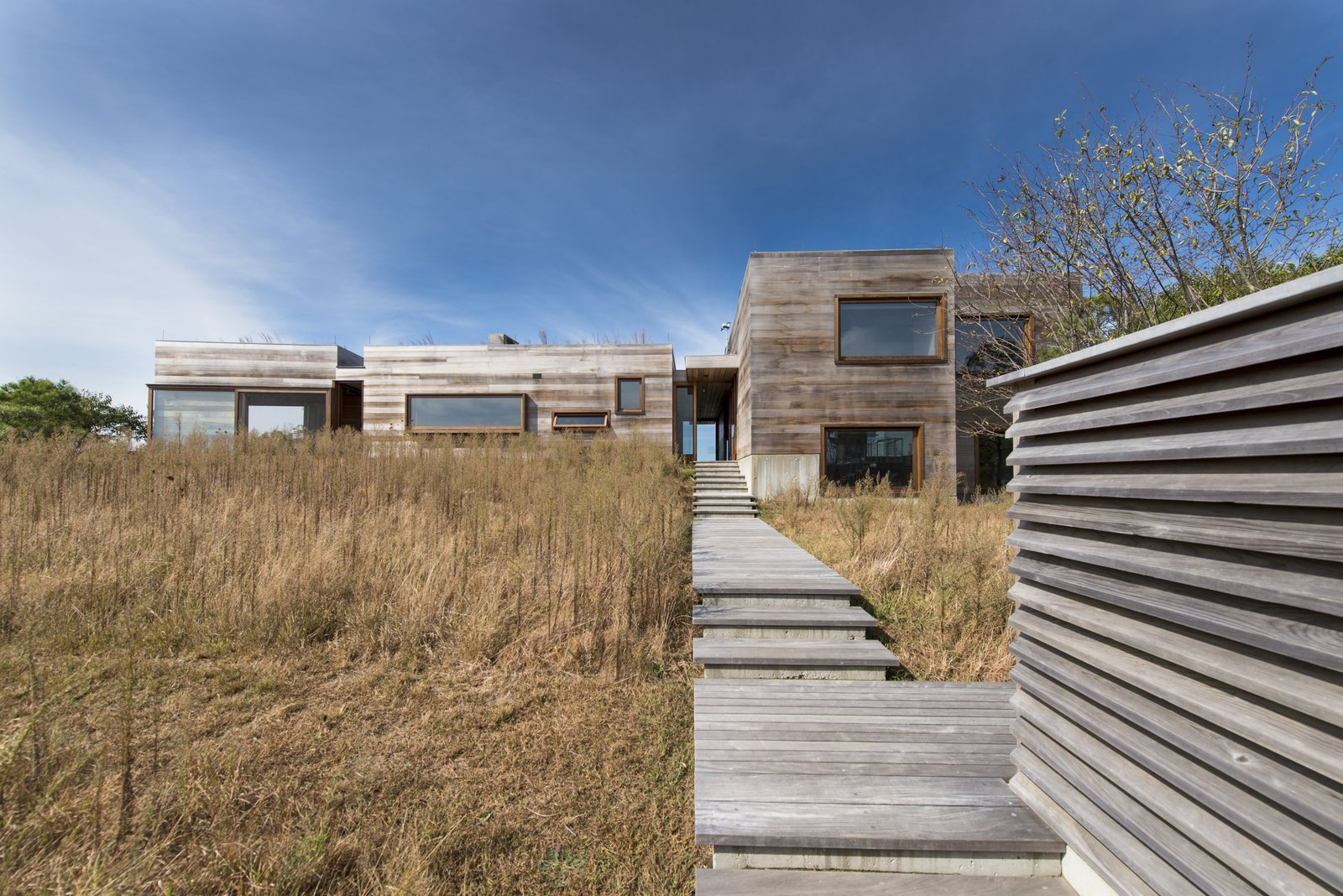 Exterior walls are clad in an sealed, unpainted western red cedar to mirror the colors of the site's tawny meadows. As the wood ages naturally, it appears as though it emerged organically from the earth.  Photo 1 of 8 in New England Vacation Home Emphasizes Island Breeze and Spectacular Views