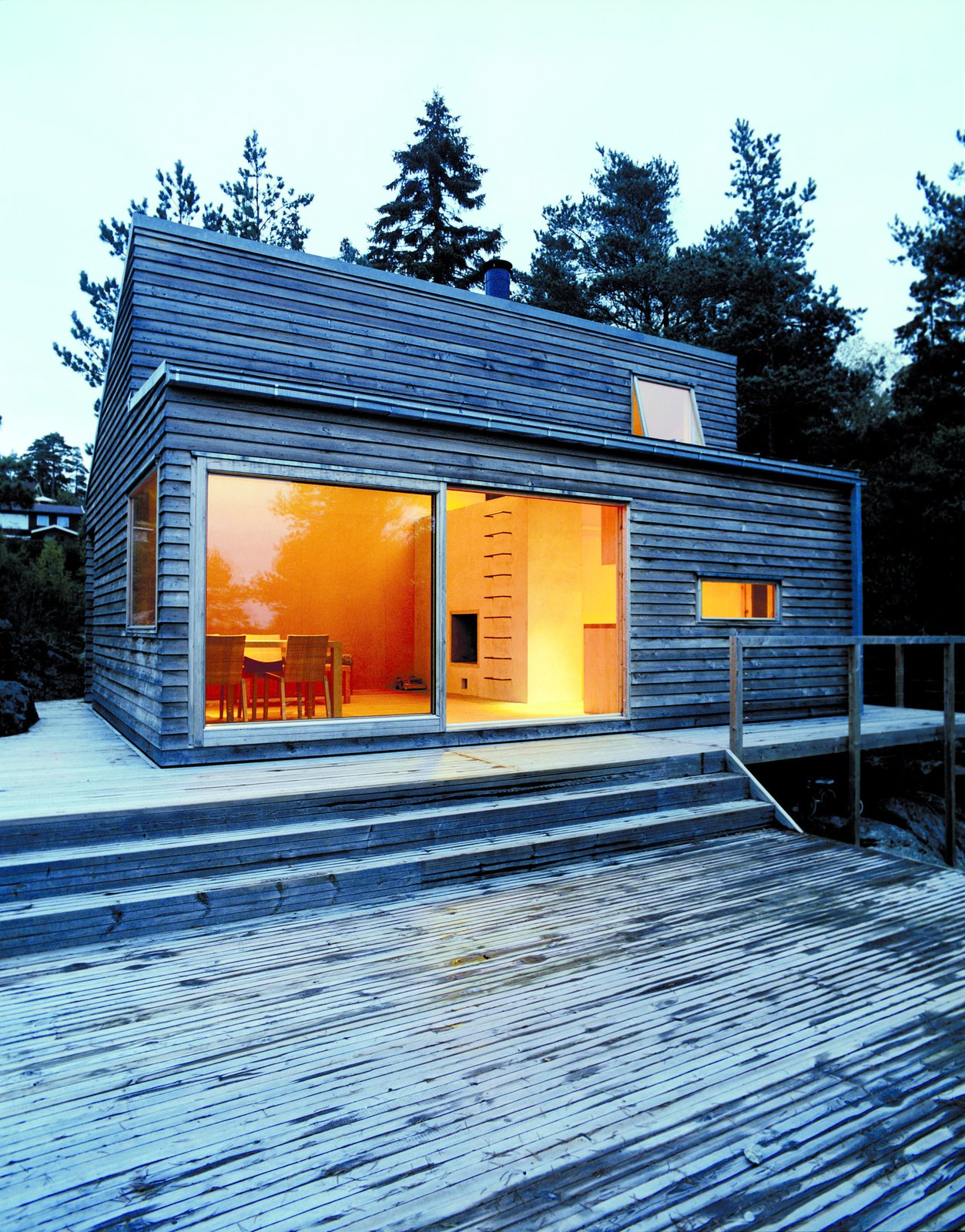 Exterior, Cabin Building Type, Wood Siding Material, Flat RoofLine, Prefab Building Type, and House Building Type Large sliding glass doors allow daylight to fill the living room. Smaller windows are placed in the kitchen area and the sleeping loft. The exterior is clad in heart pine which needs very little up-keep and is known for its strength and hardness.  Cabin from A Prefab Cabin in Norway