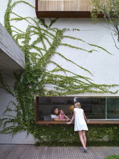 In São Paulo, Reinaldo and Piti Cóser kept green in mind when designing their deck. Here, Sophia Cóser talks to sister Helena and mother Piti through a wide, low-slung window typical of architect Marcio Kogan. Photo by: Crisobal Palma