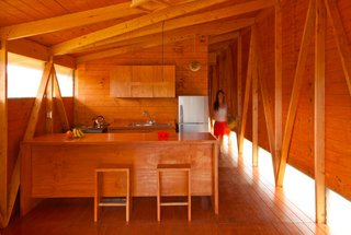 The geometric framing lining the interiors echoes the facade's asymmetrical shape. Easter Island, Chile. By AATA Arquitectos from the book Rock the Shack, Copyright Gestalten 2013.