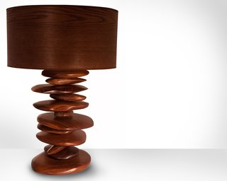 """The hand carved walnut """"rocks"""" that form the base of this Rock Pile lamp are stacked and spin independently of one another, allowing the pile to change shape. """"In contrast to the pixel style of design I often incorporate into pieces, these rocks are my way of being more freeform and not so meticulous,"""" says Michael Rupich."""