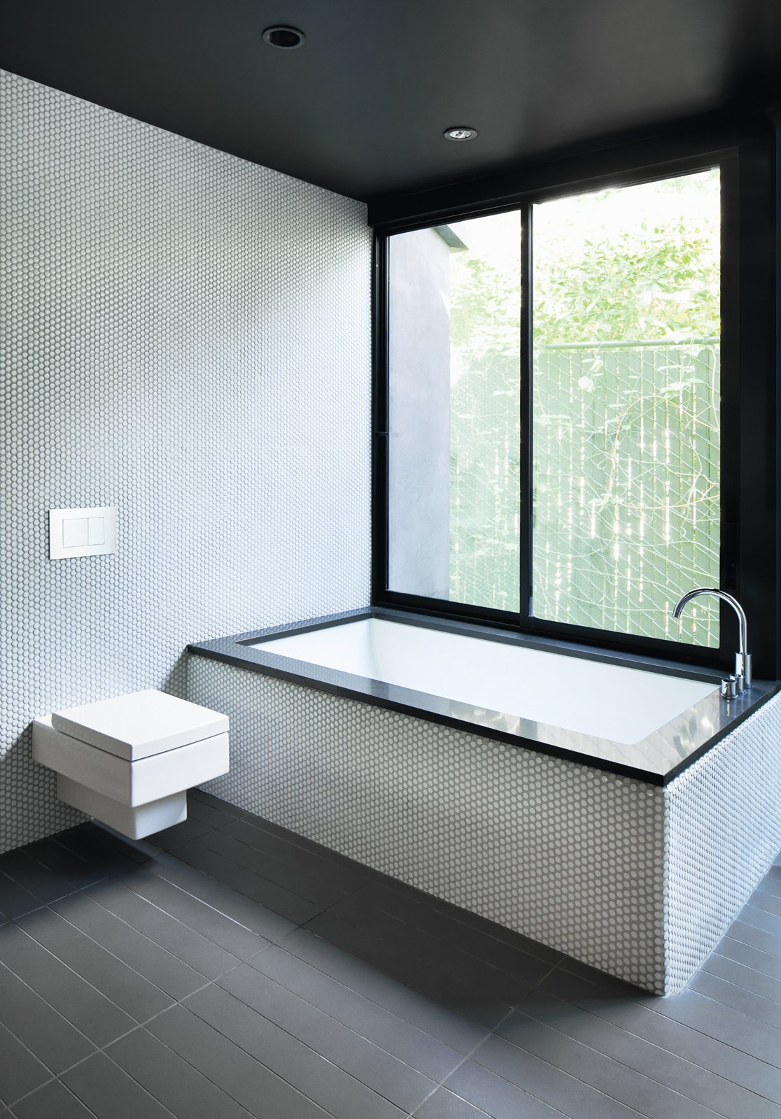"Bath Room, Ceramic Tile Floor, One Piece Toilet, Recessed Lighting, Ceramic Tile Wall, Undermount Tub, and Mosaic Tile Wall For the bathroom inside a renovated Hollywood bungalow, architect Noah Walker used a simple palette of gray and white tile, black countertops, and stainless steel fixtures. ""I love minimal bathrooms with natural light, so less is more, and pay attention to the details,"" he advises.  Bath tile"