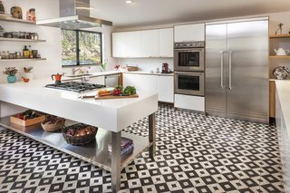 Black and white kitchen floor tiles by Granada Tile are the focal point of this airy, whimsical kitchen. A sizable island of white and stainless steel coordinates nicely with Thermador appliances and white cabinets.