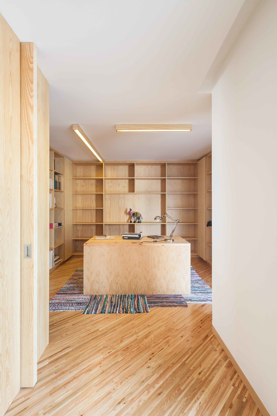 In the study, strip lighting illuminates a desk almost entirely surrounded by built-in bookshelves.  Stuff I like from Lovely Beach House is All About Angles, Stucco, and Wood