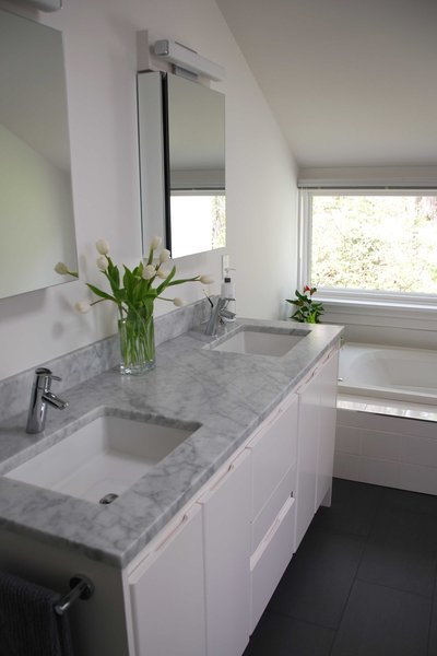 The couple picked inexpensive white porcelain tiles for the tub and shower, but splurged on a Carrara marble countertop for the double vanity. The medicine cabinets are by Fresca.  Bath Reno from North Carolina Home Renovated with a Swiss Aesthetic in Mind