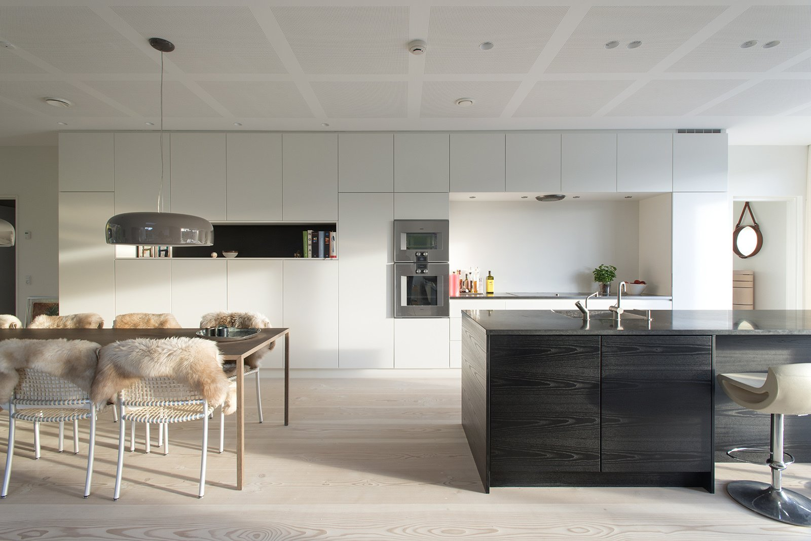 Kitchen, White Cabinet, and Light Hardwood Floor Built-in kitchen cabinets and a monolithic island help keep the space uncluttered. The wall ovens are from Gaggenau.  Kitchen