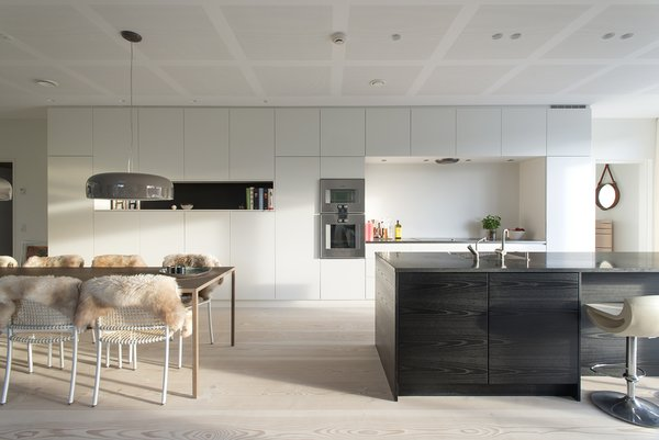 Built-in kitchen cabinets and a monolithic island help keep the space uncluttered. The wall ovens are from Gaggenau.
