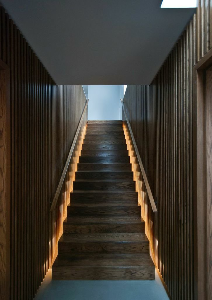 The house's central staircase is encased in oak paneling, which brings added warmth and texture to the ground floor. The wide steps rise to the second floor, which houses three bedrooms and bathrooms.  190+ Best Modern Staircase Ideas from London Industrial Compound Converted Into Modern Housing