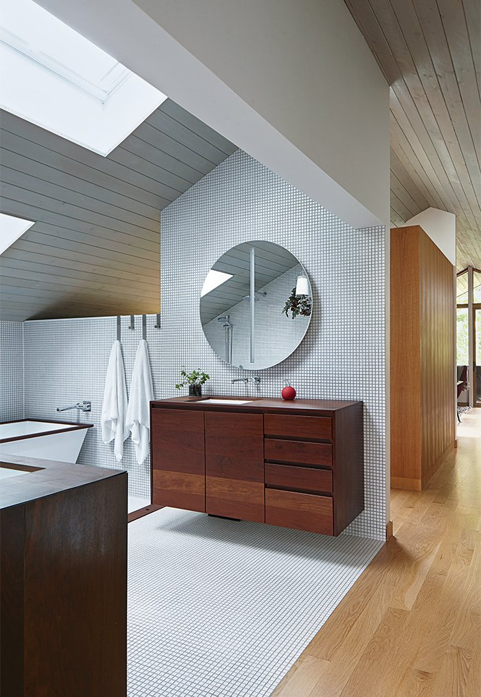 The master bathroom has an aluminum-shell tub with an ipe-slat basin, and a pair of solid-walnut vanities, all designed by Hufft Projects. Tagged: Bath Room, Undermount Sink, and Wall Mount Sink.  Photo 9 of 10 in This Kansas City Home Looks Like Its Neighbors, But Reveals a Truly Modern Sensibility