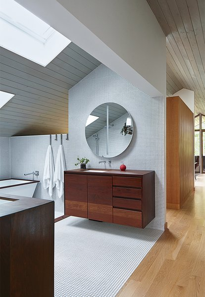 The master bathroom has an aluminum-shell tub with an ipe-slat basin, and a pair of solid-walnut vanities, all designed by Hufft Projects.