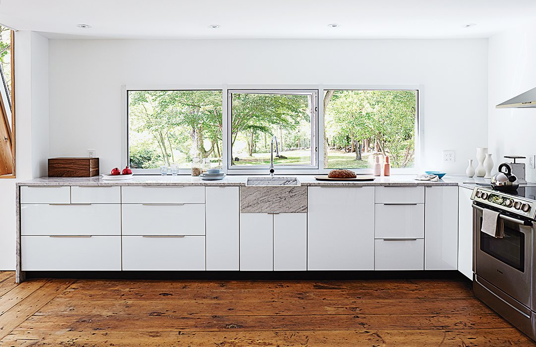 The new custom kitchen is situated in the original structure. The window is a new commercial unit with an operable frameless center pane and was set so that the countertop could tuck right underneath it to create a 1/4-inch shadow line.  Photo 7 of 22 in A Mind-Bending Renovation Brings a Bold, Modern Addition to an Old Farmhouse