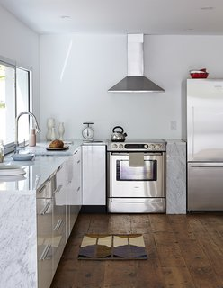 The updated kitchen is outfitted with stainless steel appliances, including a Bosch range, a Fisher & Paykel refrigerator, and a Frigidaire range hood. The faucet is Hudson Reed.